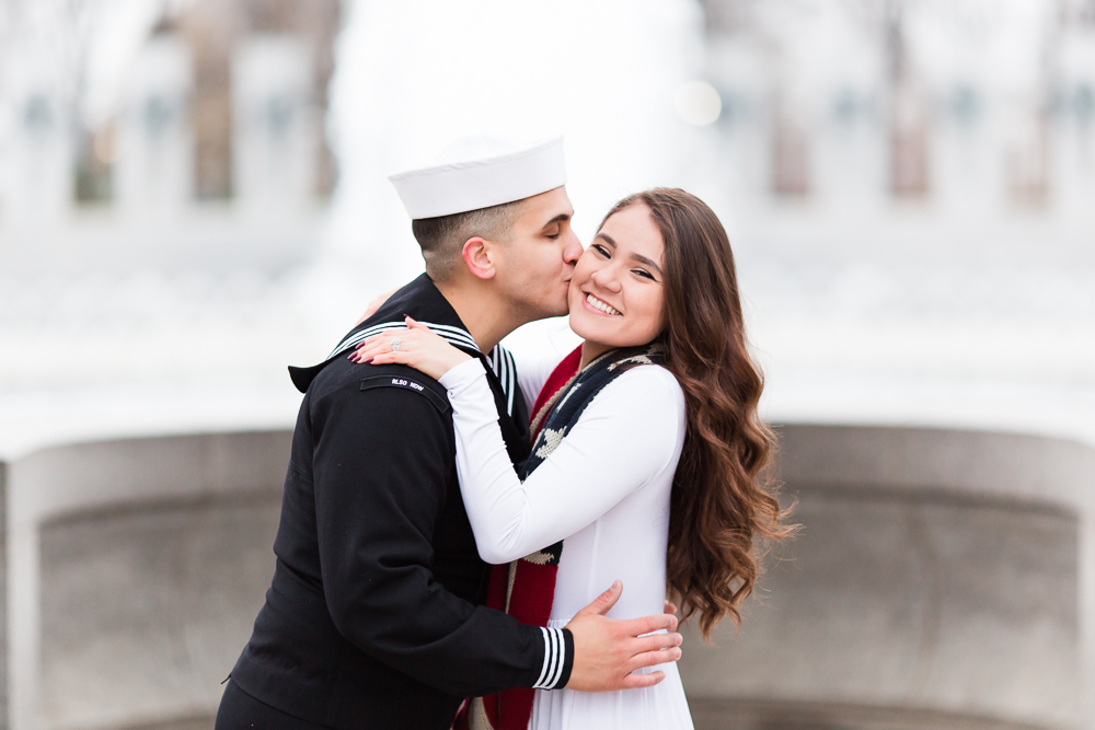 Military groom giving his bride a kiss on the cheek by the World War II Memorial fountain on the National Mall