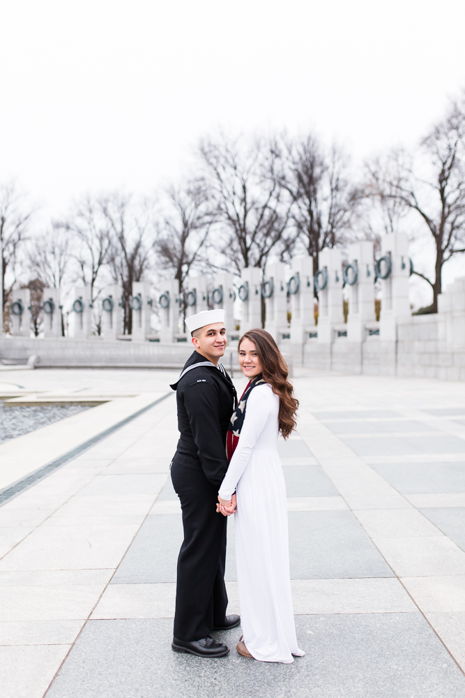 Wedding couple holding hands in the plaza of the World War II Memorial in front of the granite pillars