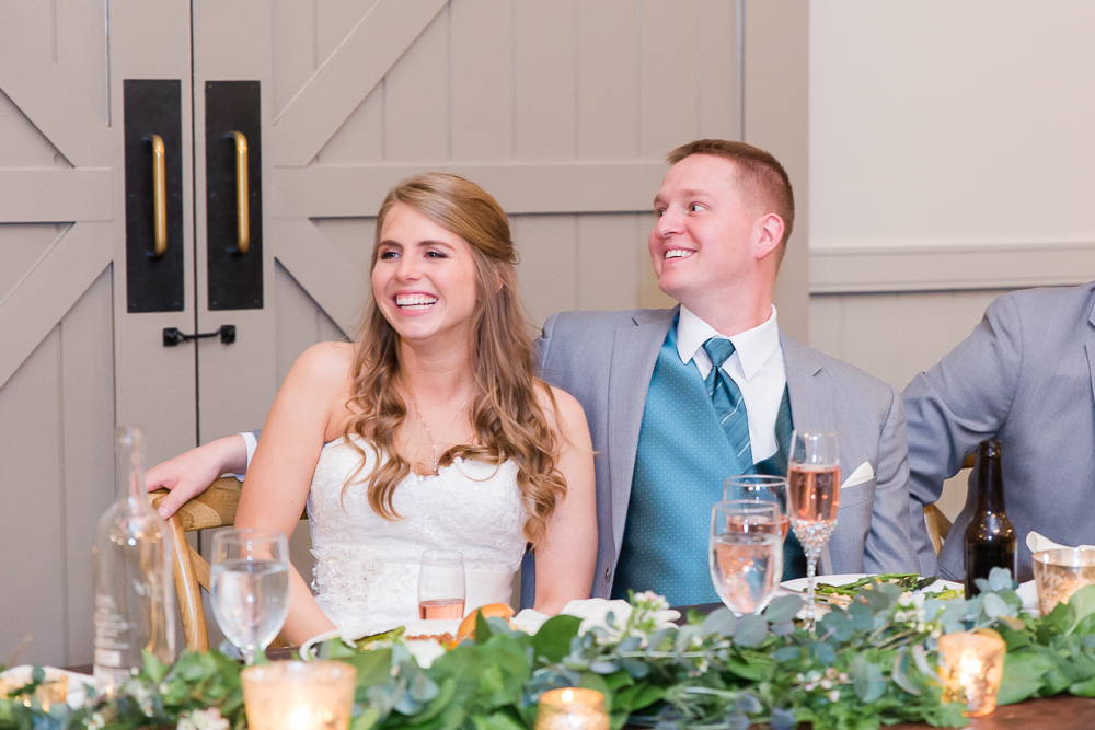 Candid photo of bride and groom laughing during the toasts at their wedding reception