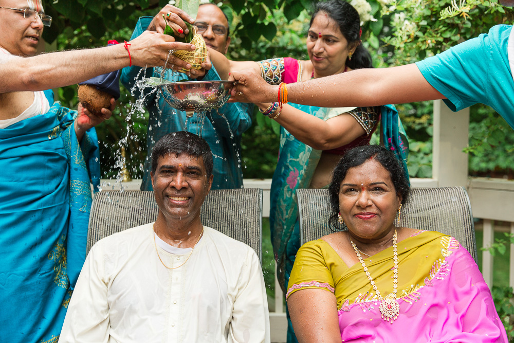 Husband and wife having water poured over their heads during Hindu vow renewal ceremony | Best Hindu Wedding Photographer in Northern Virginia