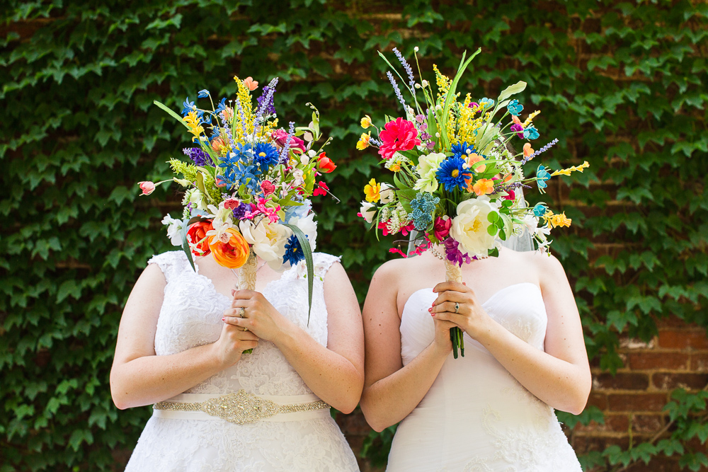 Two brides holding rainbow bouquets on their wedding day | Same sex wedding photographer in Northern Virginia