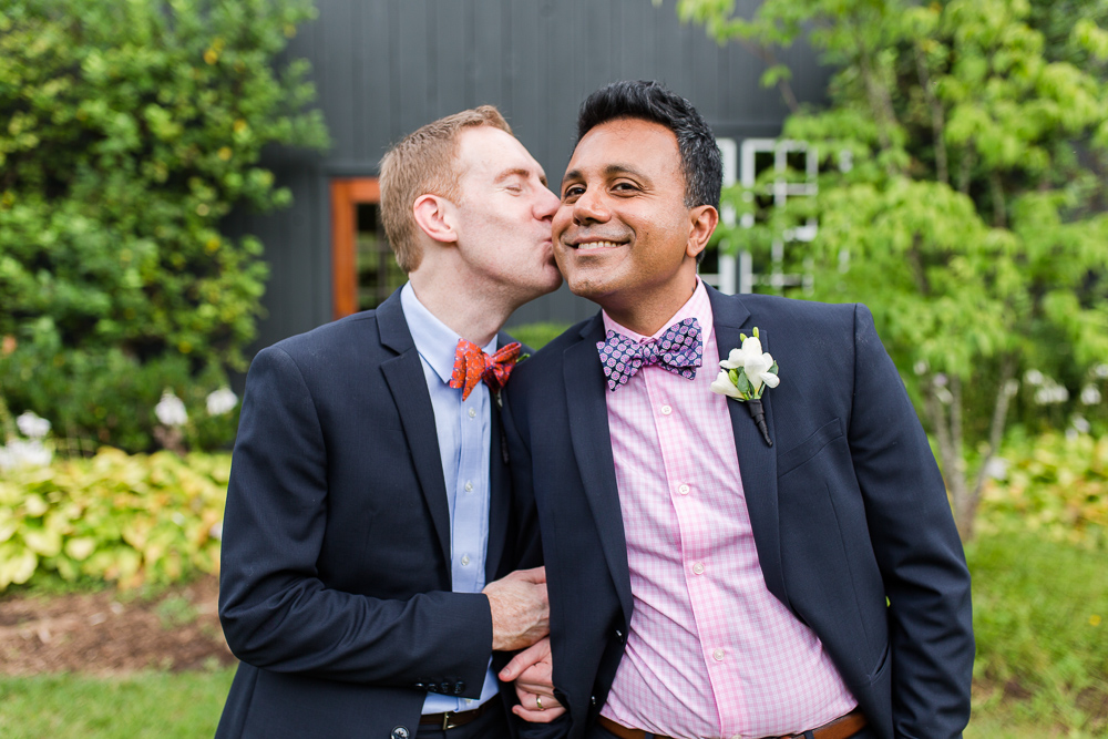 Groom kissing his husband on the cheek outside of the barn wedding venue | LGBT Wedding Photography in Northern Virginia