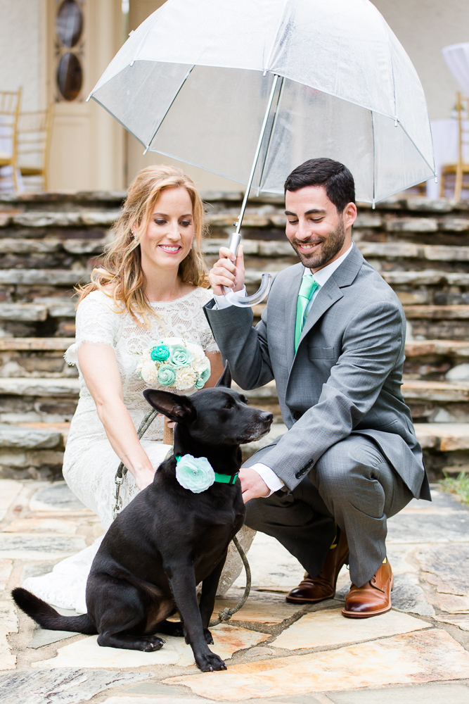 Bride and groom with their dog in front of the steps of Rust Manor House