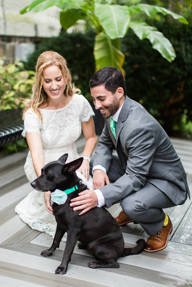 Husband and wife with their dog of honor in the magnolia grove at their wedding venue | Leesburg Wedding Photography