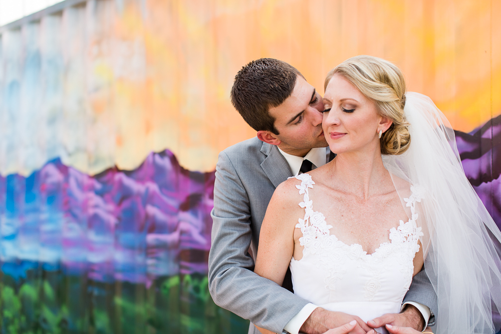 Groom giving bride a kiss on the cheek in front of a colorful mountain mural | Colorful Northern Virginia Wedding Photography