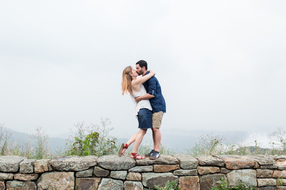 Engaged couple kisses while standing on a rock wall on Skyline Drive | Blue Ridge Mountain engagement photography