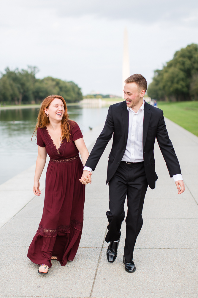 Couple laughing as they hold hands and walk along the Reflecting Pool | Best DC candid engagement photographer