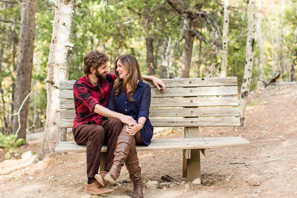 Engaged couple sitting on a bench during their fall engagement session in the woods | Northern Virginia adventure engagement photographer