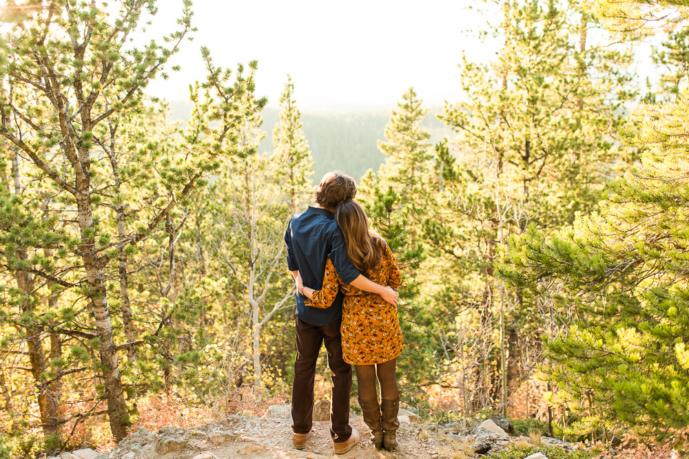 Couple hugging as they look out over the forest during their hiking engagement photos
