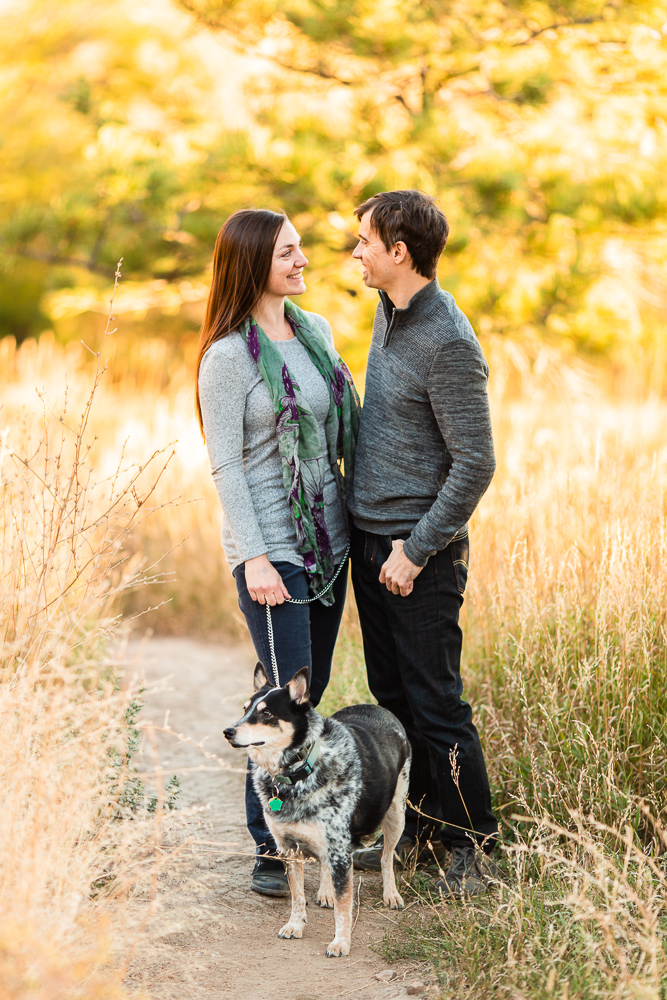Smiling couple with their cattle dog during a hiking engagement shoot