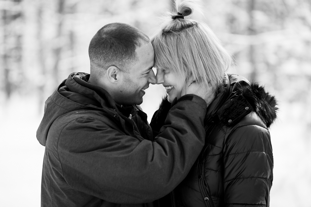 Smiling couple leans in for a kiss during their chilly winter engagement shoot in Reston, Virginia | DC engagement photographer