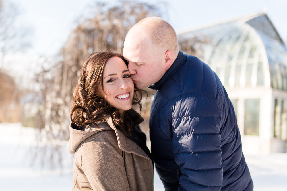 Giving his fiance a kiss on the cheek during their engagement pictures in front of the Lamberton Conservatory in Rochester, New York