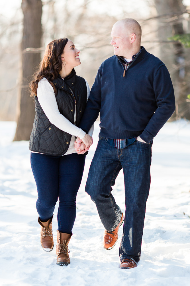 Holding hands while they walk in the snow at Highland Park | Rochester, NY engagement photographer