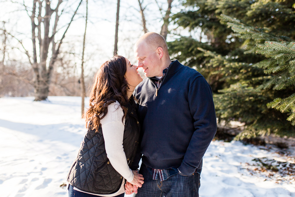 Engaged couple cuddles up close during a cold winter day in Highland Park