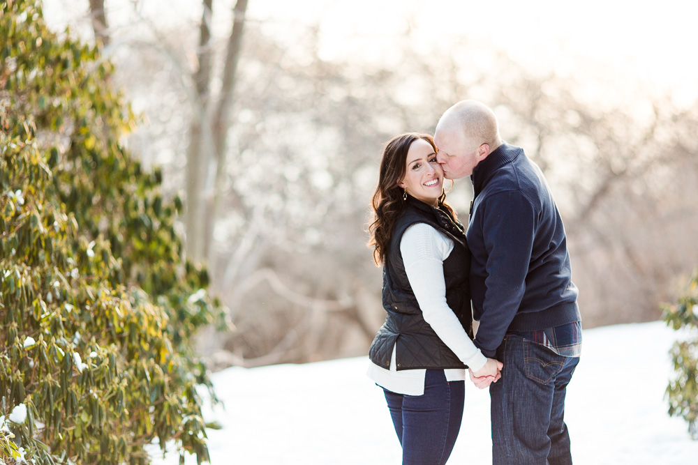 Stopping for a kiss on the cheek as they walk the trails at Highland Park | Best Rochester, NY engagement photo locations