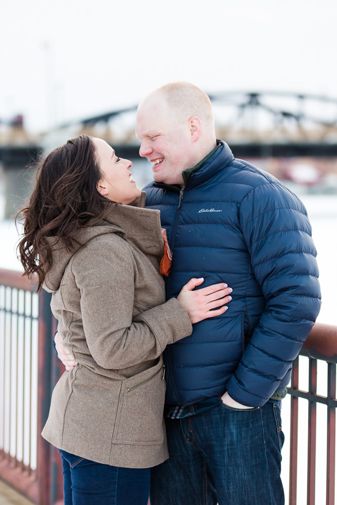 Engaged couple cuddling close to keep warm on a snowy day along the Genesee River near the Ford Street Bridge | Rochester, NY Engagement Photographer