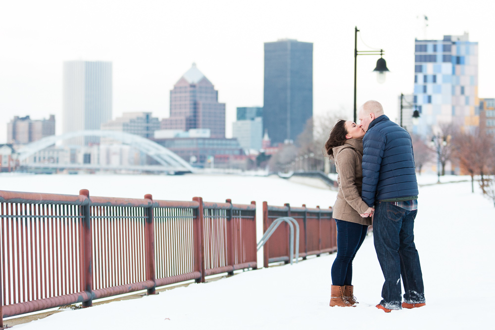 Couple kissing on the Genesee Riverway Trail with Rochester skyline behind them during a snow engagement shoot