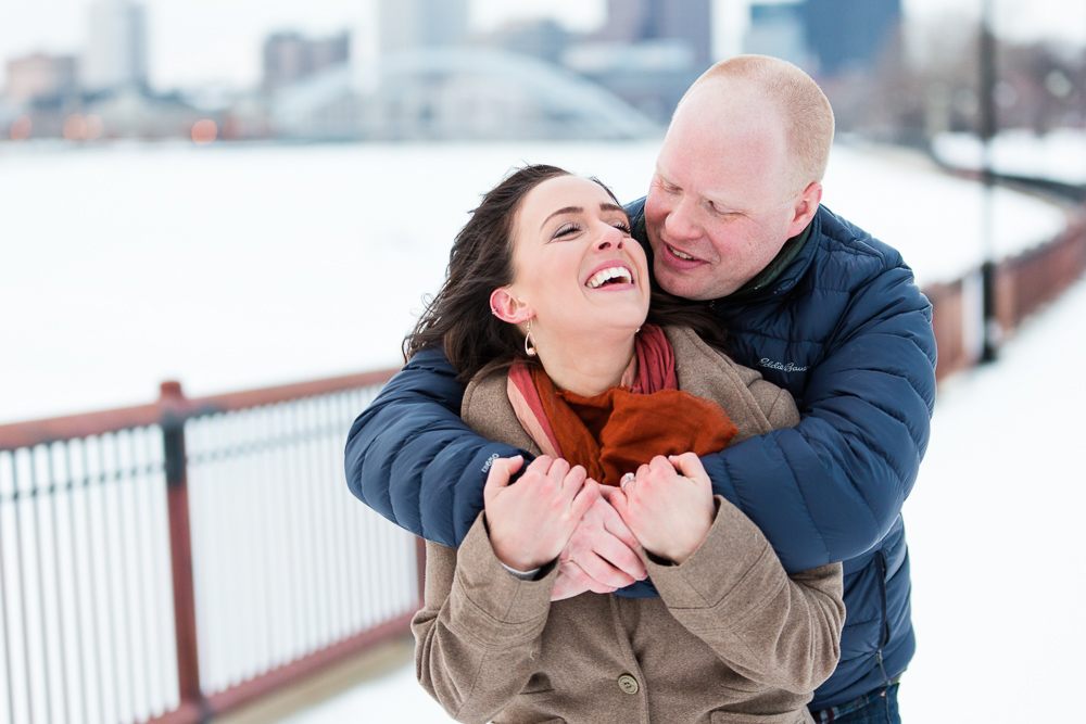 Couple laughing while groom-to-be gives his fiance a big bear hug on a cold winter day along the Genesee River