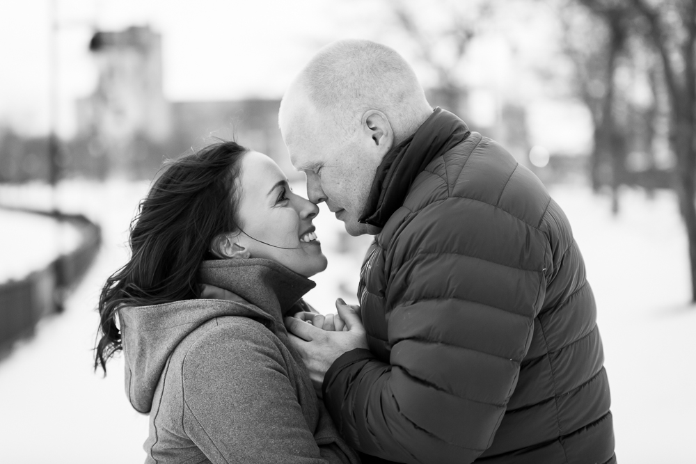 Couple holding hands and snuggling close to keep warm during their winter engagement on the Genesee Riverway Trail in Rochester, NY