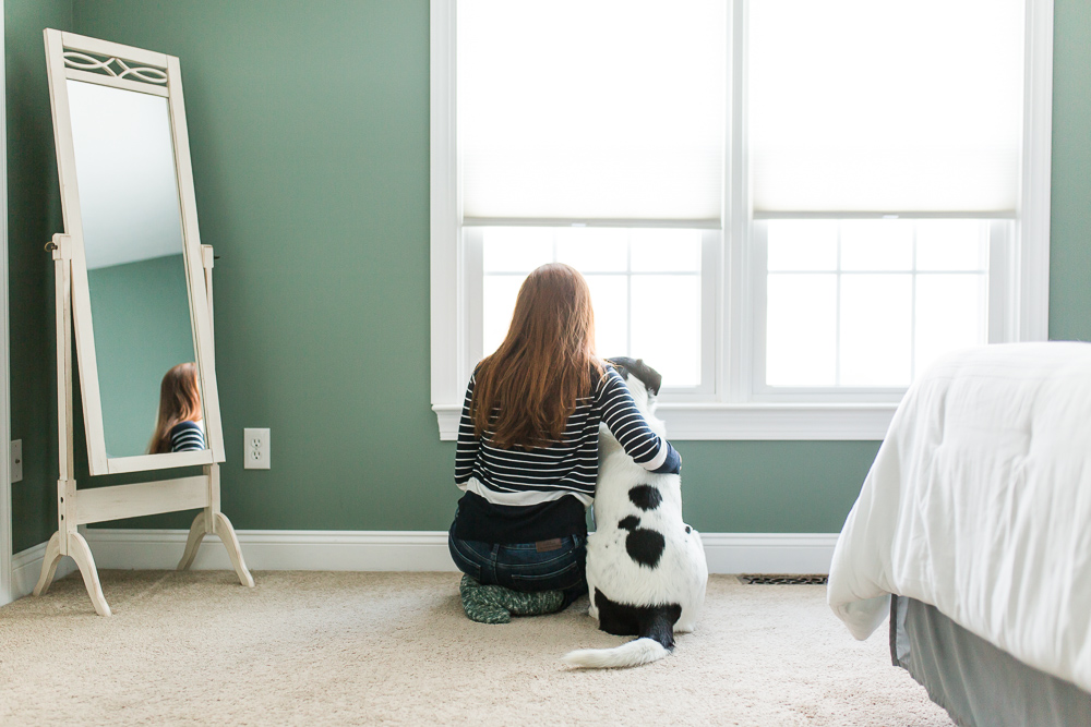 Dog and his mom sitting on the bedroom floor and looking out the window