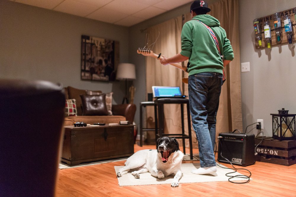 Dog yawning while dad plays the guitar