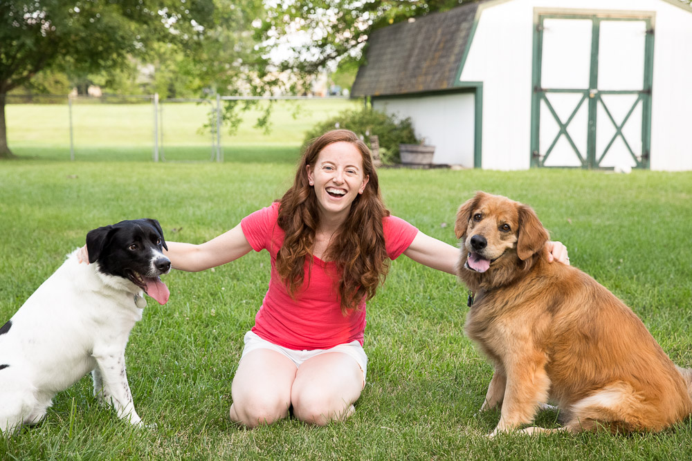 Laughing dog mom with golden retriever and black and white rescue dog