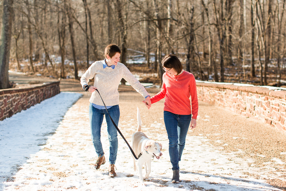 Engaged couple walking with their dog through the snow on the Stone Bridge of Manassas Battlefield Park | Dog engagement photos in Northern Virginia