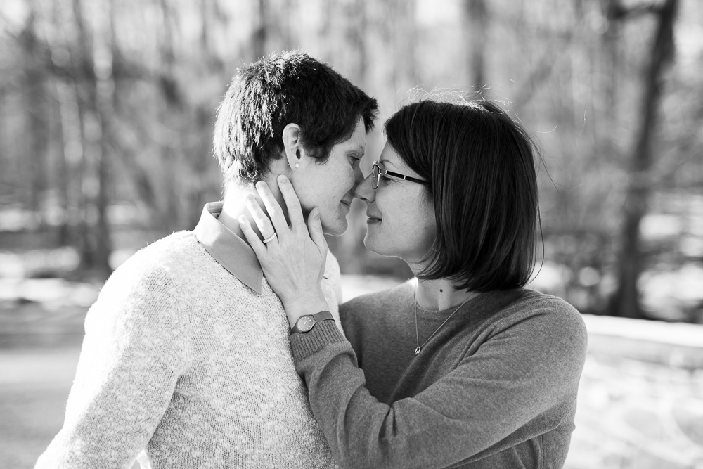 Black and white photo of lesbian couple leaning in for a kiss on the bridge | Manassas Engagement Photographer