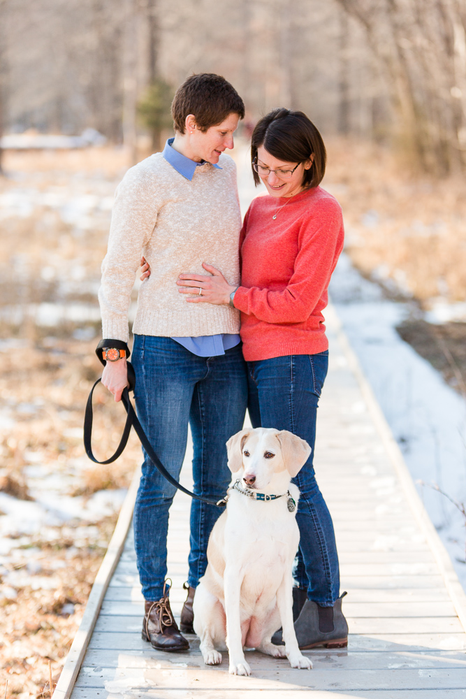 Engaged couple on the boardwalk with their rescue dog during a snowy photo shoot in Manassas, Virginia