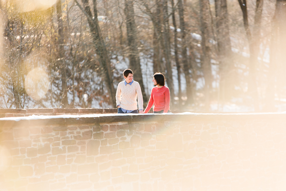 Engaged lesbian couple holding hands as they walk across the Stone Bridge | Northern Virginia same-sex engagement photos