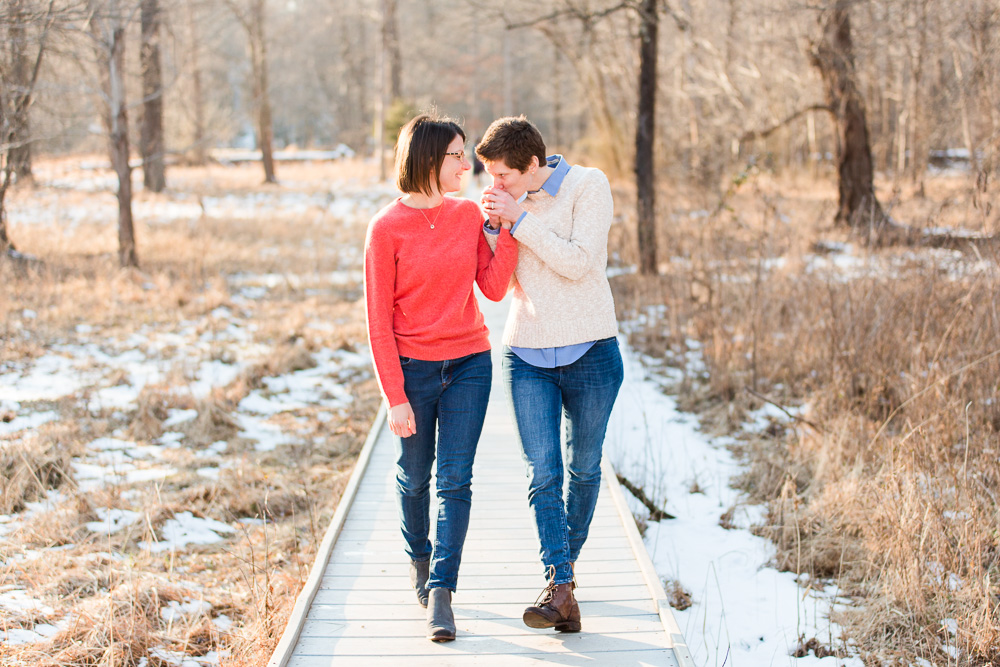 Giving her fiancee a kiss as they walk on the boardwalk during winter engagement session at Manassas Battlefield