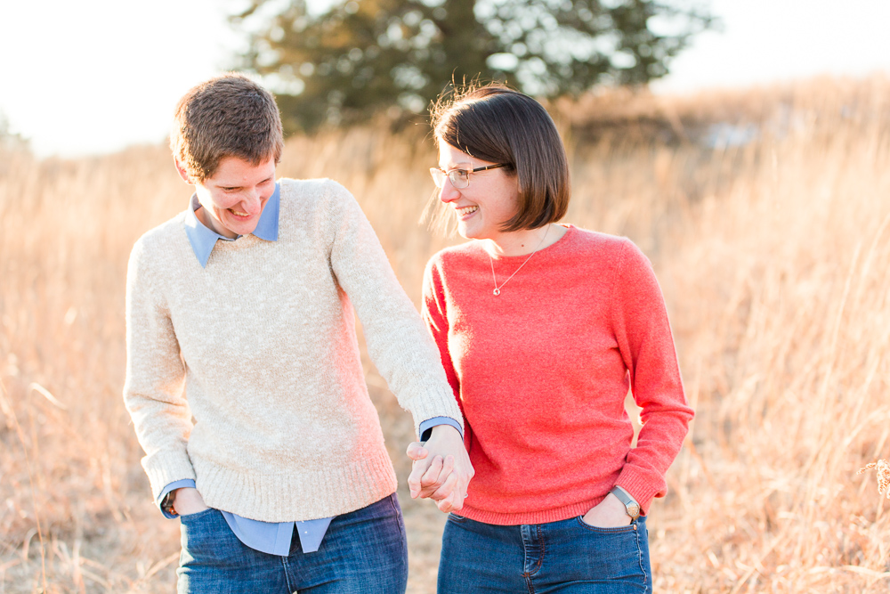 Laughing as they walk through the tall grass during golden hour engagement photos in Manassas, Virginia