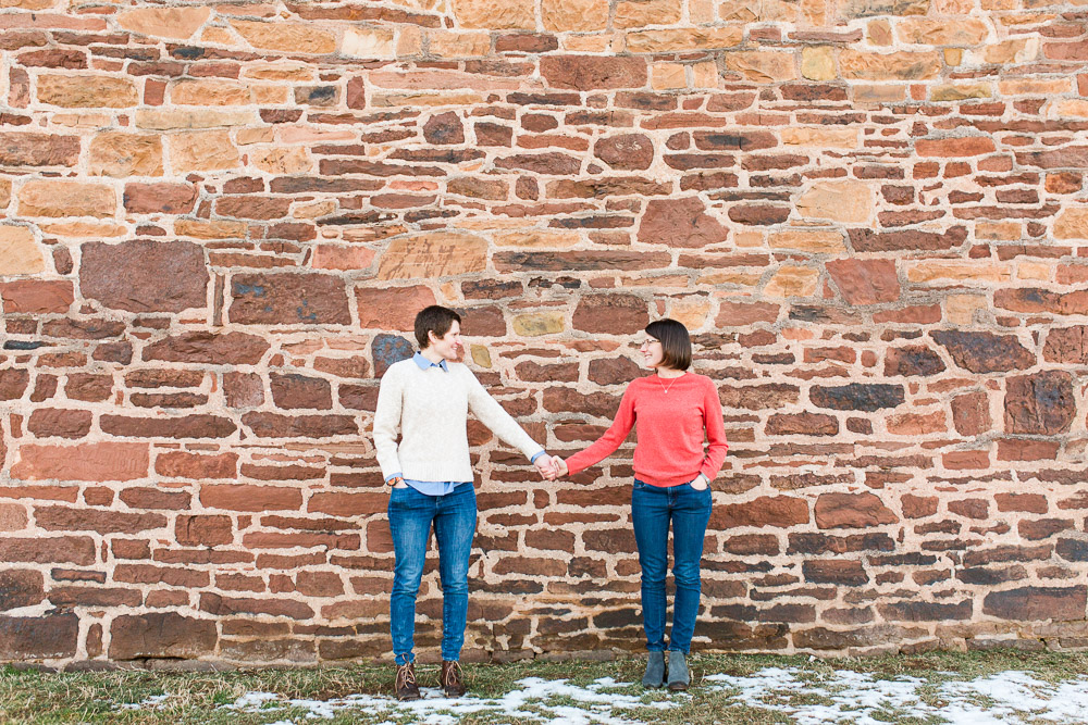 Lesbian couple holding hands next to the wall of the Stone House | Best Northern Virginia engagement photo locations