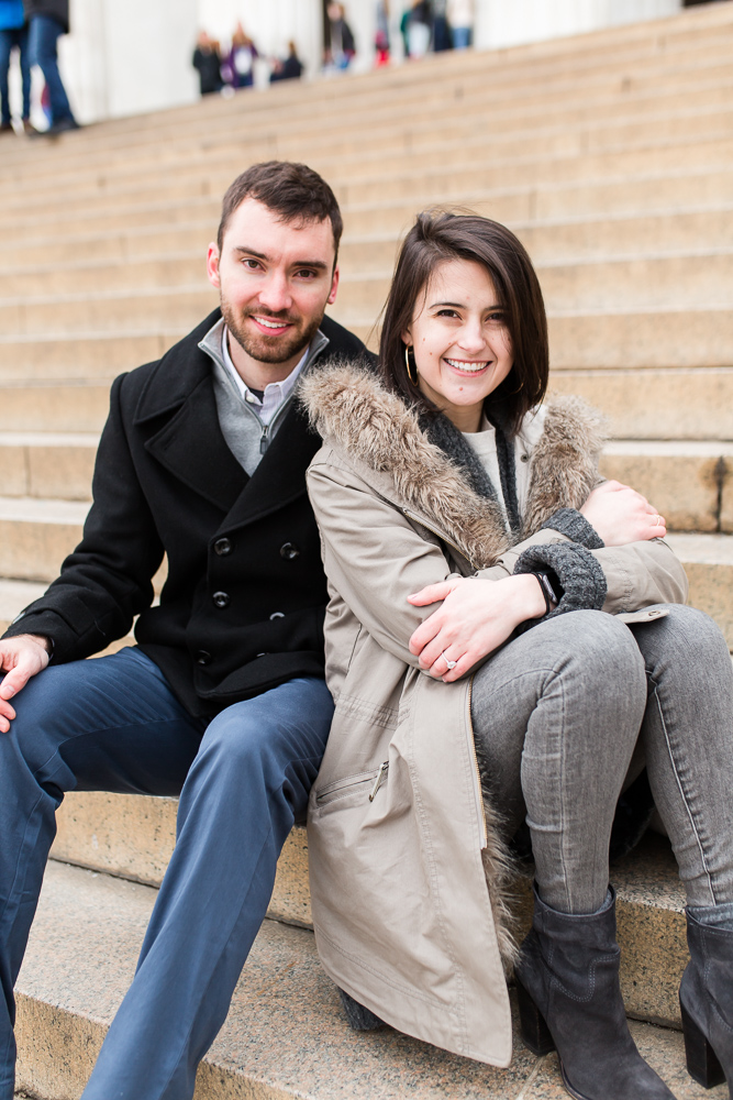 Newly engaged couple sitting on the steps of the Lincoln Memorial