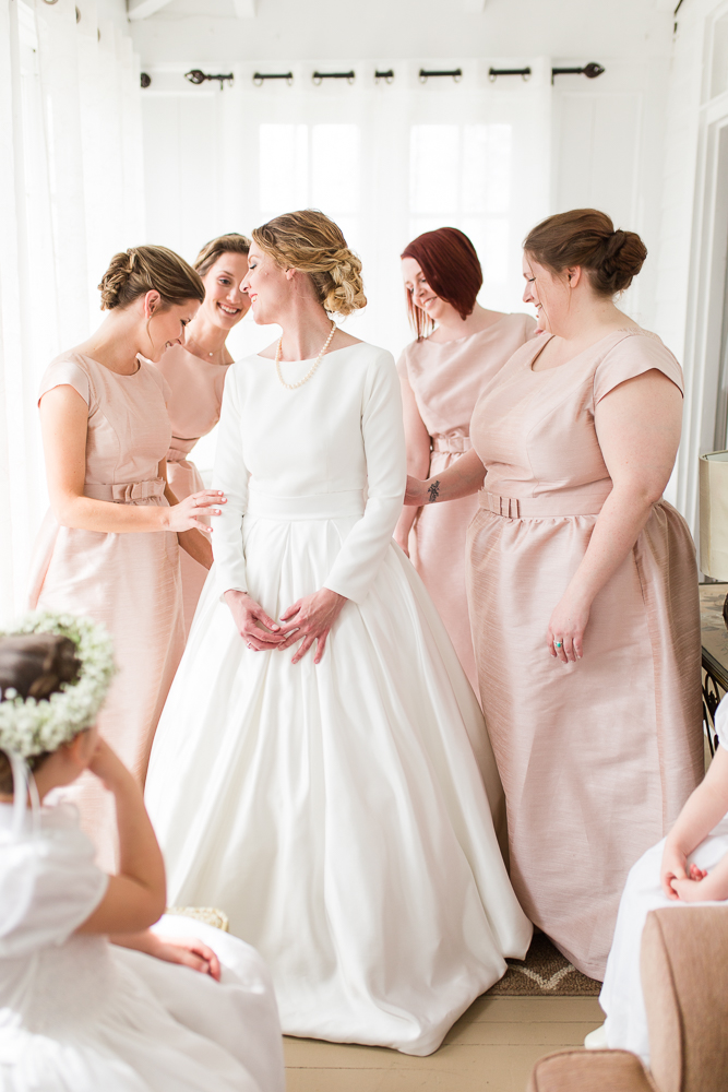 Bride with her bridesmaids in ballet pink dresses, getting ready in the bridal suite at Black Horse Inn