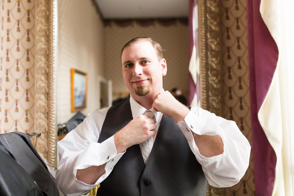 Groom smiling at the camera as he straightens his tie | Warrenton, Virginia wedding