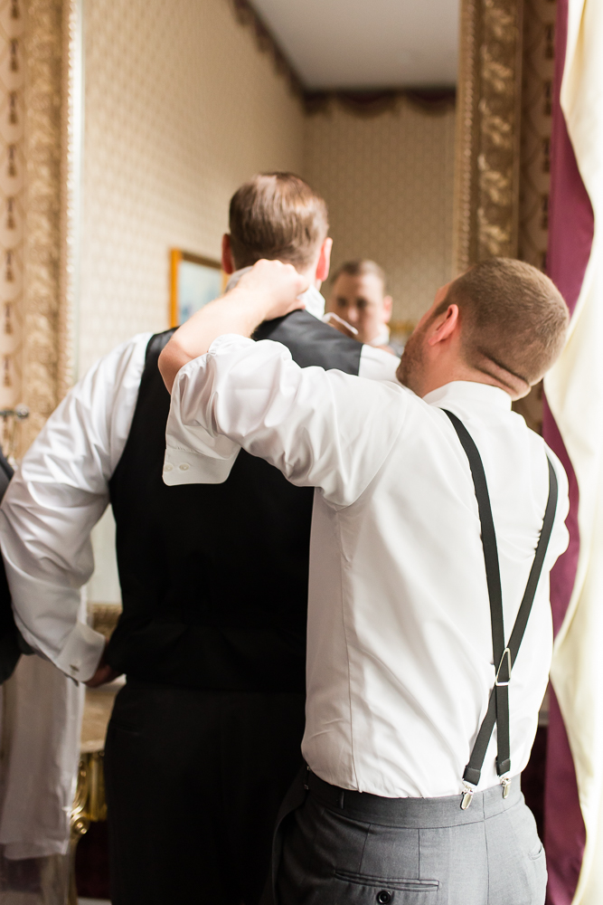 Groomsmen helping the groom put on his tie in the Gilded Fox Ballroom at the Black Horse Inn