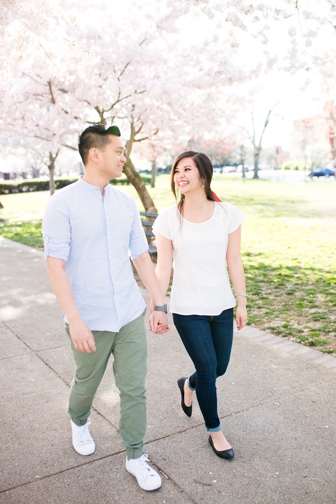 Smiling couple walking underneath the cherry blossoms during their spring engagement session