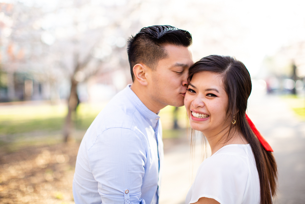 A kiss on the cheek at the cherry blossoms in Washington, DC | Cherry blossom engagement pictures