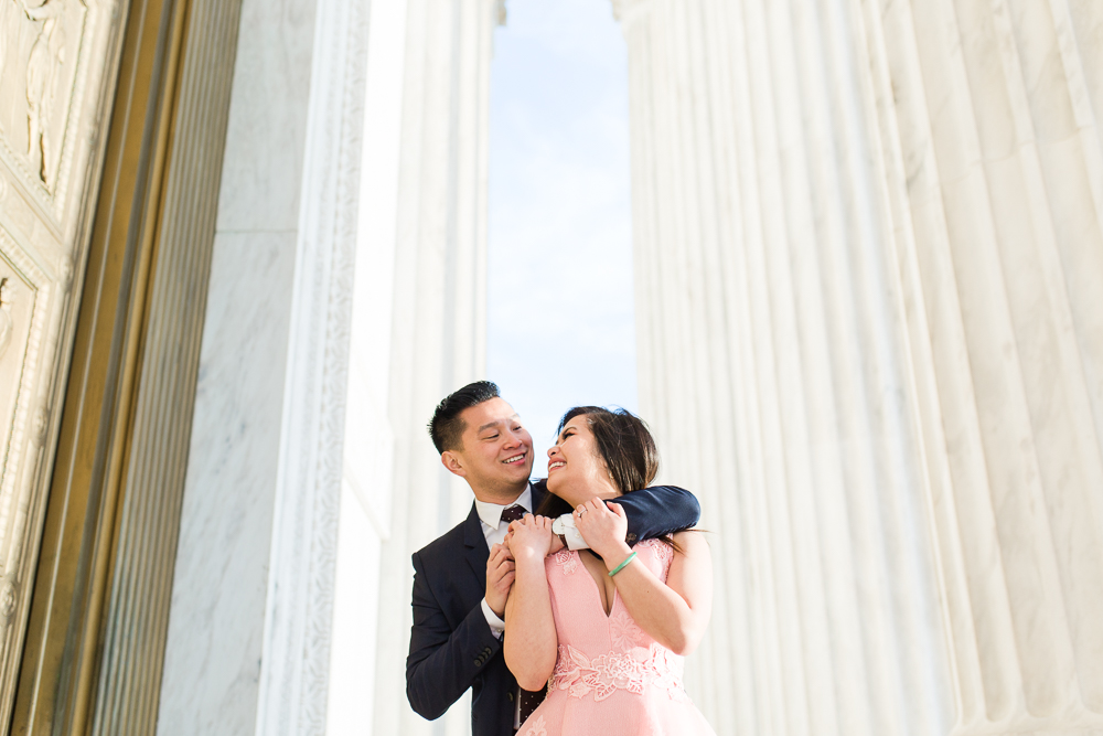 Engaged couple standing between the columns of the Supreme Court building in Washington, DC | Classic DC engagement photos