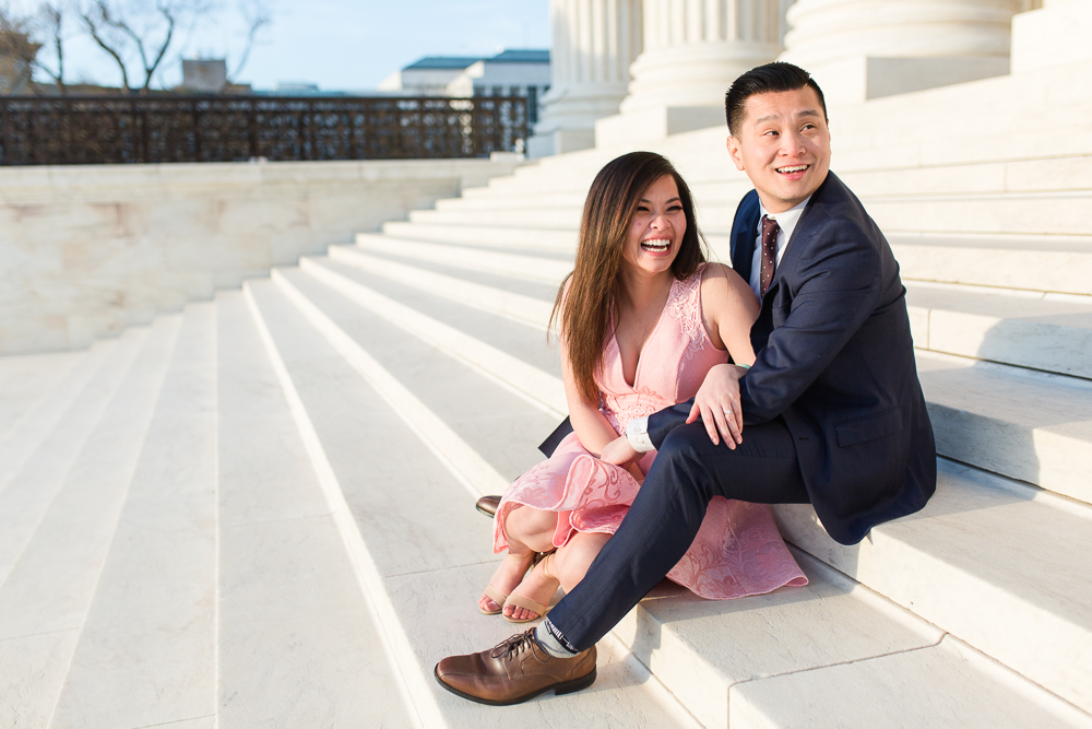 Candid engagement picture of couple laughing while sitting on the white steps of the Supreme Court