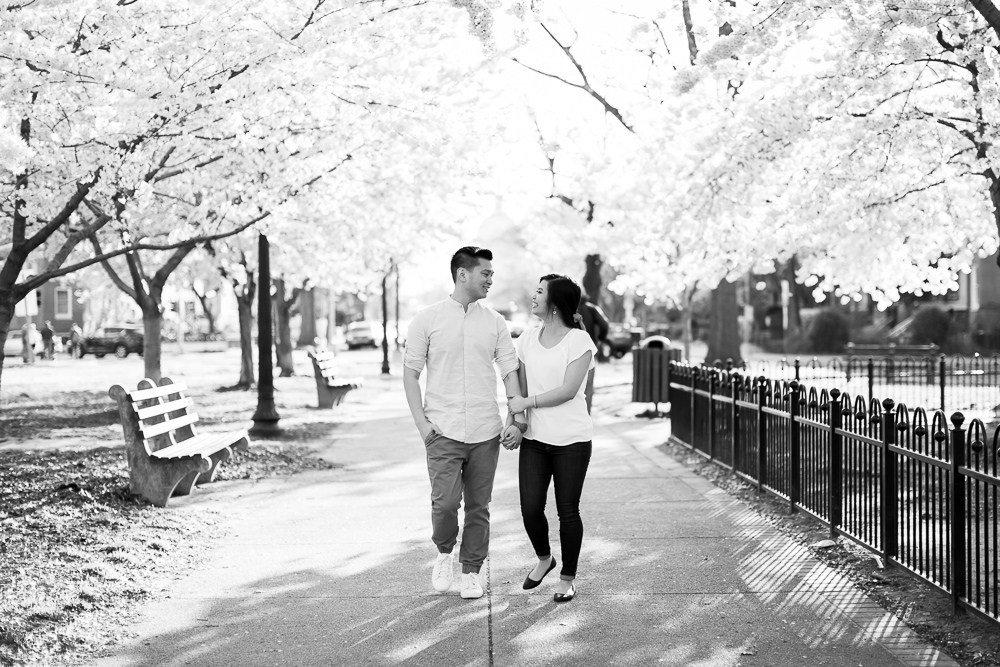 Engaged couple holding hands as they walk along the sidewalk during a spring engagement session