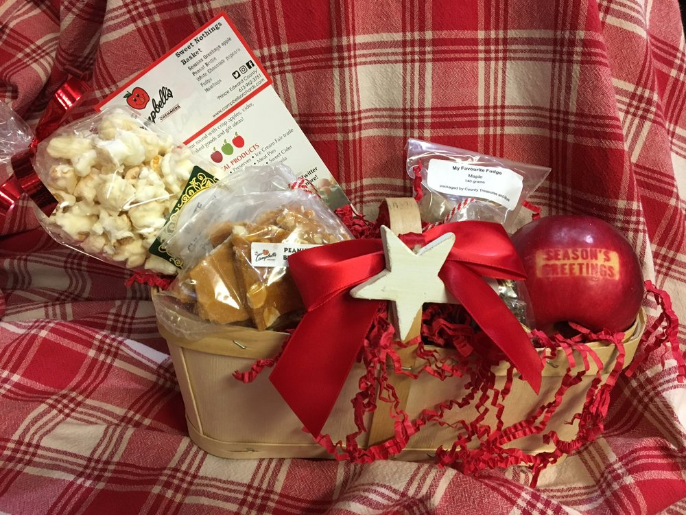 sweet nothings gift basket - $35 Seasons Greetings Apple 170g peanut brittle 100g White Chocolate Popcorn 140 g My Favourite Fudge 220 g Humbugs Presented in a 2 Quart basket with candy canes and festive bow