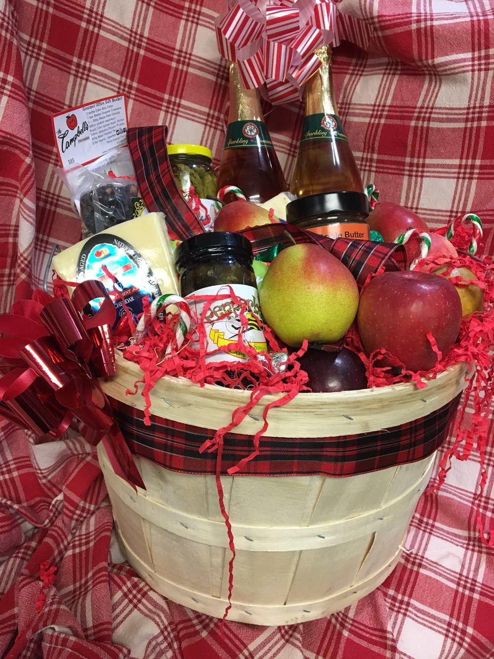 Gourmet office gift basket - $85 2 bottles of Cider Keg Cider 1 box Breton Organic Crackers 2 -250g Maple Dale Cheese 500ml Pickled Asparagus 1-250ml Angry Cats Spiced Apple Butter 236ml Jalapeno Pepper Pickles 400g Black Shelled Peanuts 5 lbs Assorted Apples Presented in a half bushel basket brimming with apples and candy canes and kisses
