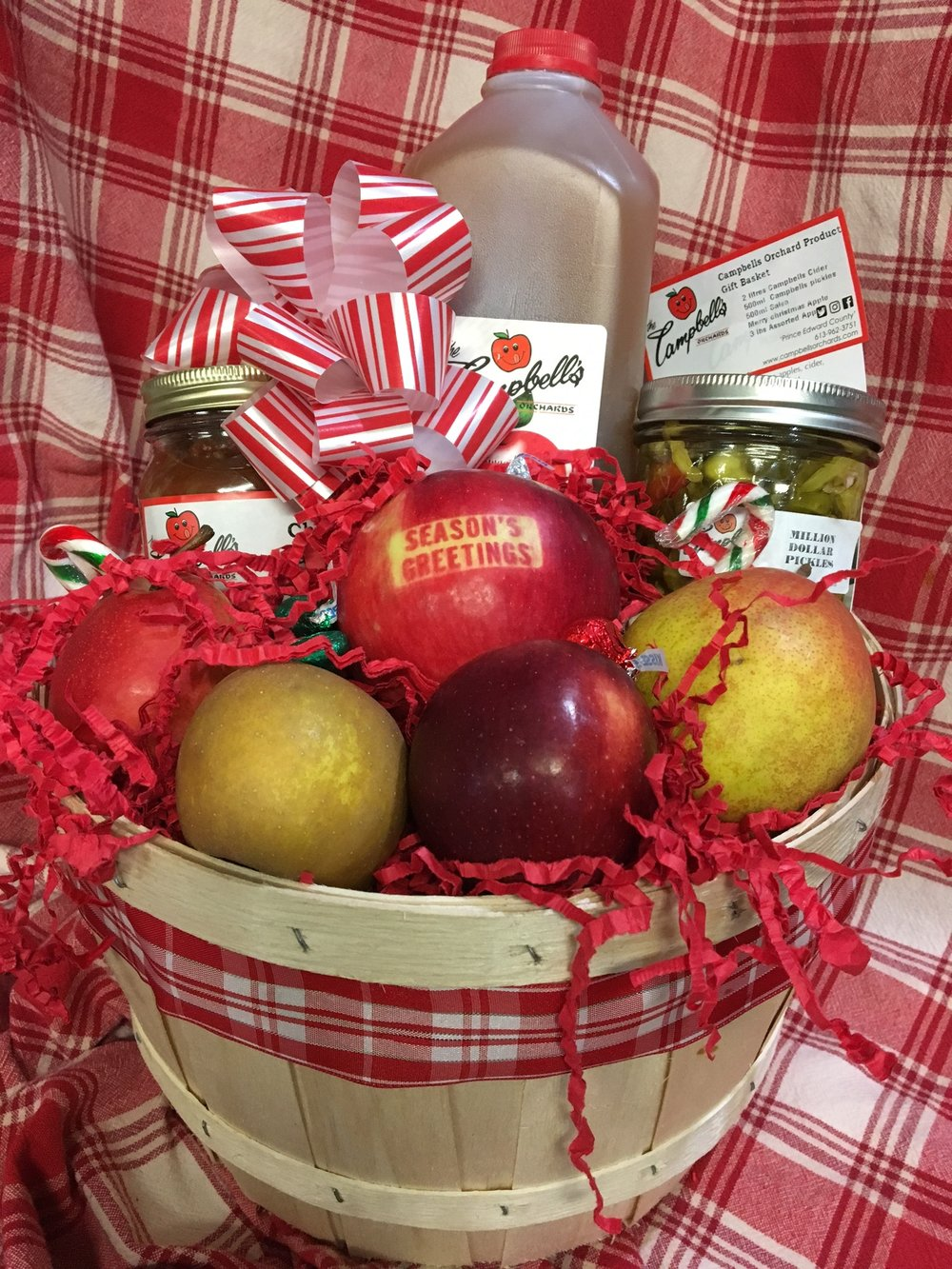 Campbell's Orchard Product Gift Peck Basket - $60 2 litres Campbells Fresh Sweet Cider 500ml Campbells pickles 500ml Campbells Salsa Merry Christmas Apple 3 lbs Assorted Apples Presented in a Peck Basket filled with apples and topped with candy canes and a bow