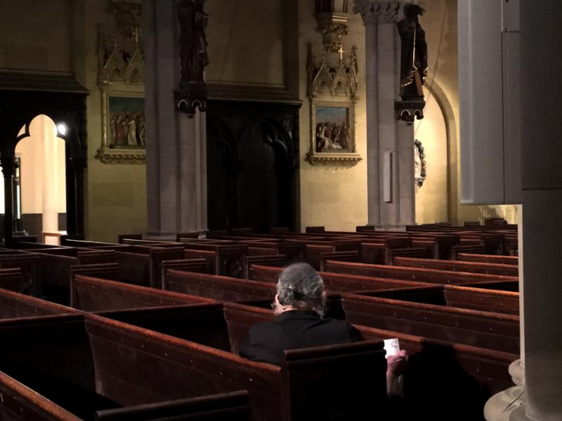 A visitor praying in the church .
