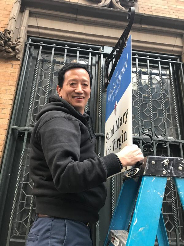 Sexton Harka Gurung hanging a new sign    on 47th Street.