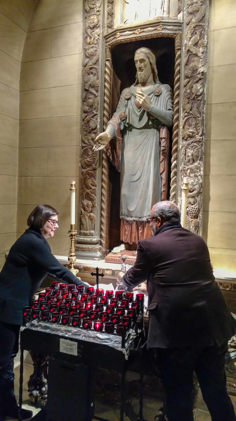 Ushers Renee Pecquex and Blair Burroughs collect the bread and wine at the Sacred Heart Shrine before the preparation of the gifts.