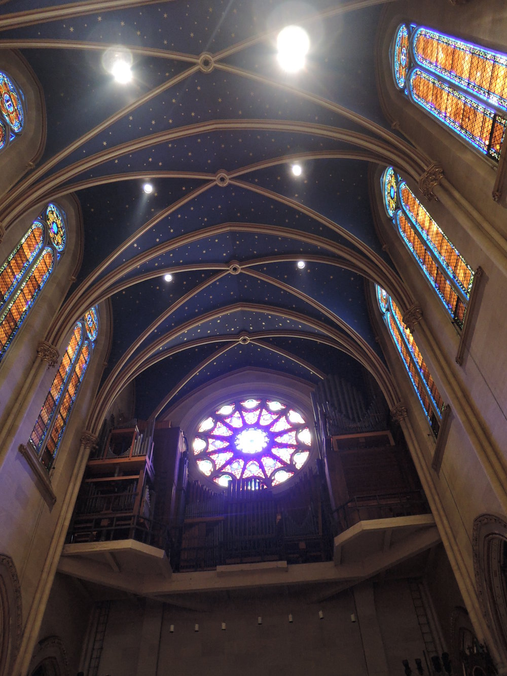 A view of the ceiling, double lancet windows, organ, and rose window from the main aisle