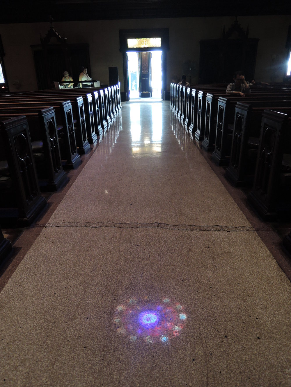 A reflection of the rose window on the floor of the main aisle of the church